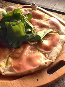 『夢や』裏の畑で作るルッコラを載せた生ハムとルッコラのピザ